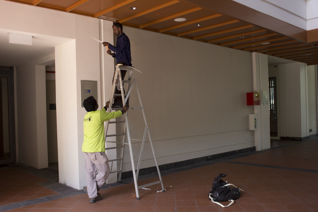 Workers fixing gaps in the ceiling at East Core on Aug. 17. (Regina Marie Lee)