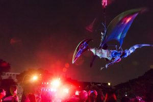 A masked performer rides a pterodactyl from the top of the National Museum to the ground